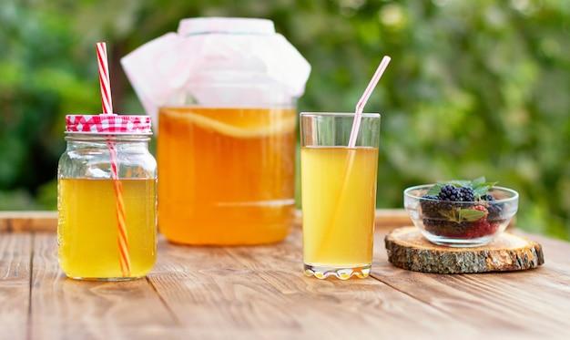 Frasco de vidrio con kombucha, un vaso vertido con kombucha y una taza con moras en un jardín de verano.