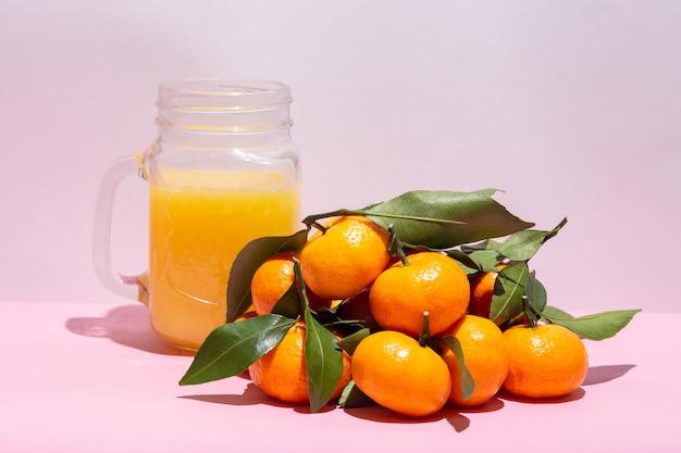 Frasco de vidrio con mango de jugo de cítricos dieta de desintoxicación bebida saludable jugo de mandarina mandarinas crudas