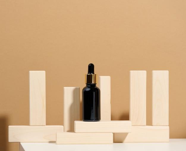 Frasco de vidrio marrón con pipeta se encuentra sobre una mesa blanca. branding de cosméticos spa. embalaje para gel, suero, publicidad y promoción de productos, maqueta.