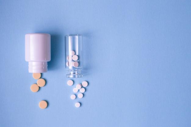 Frasco de vidrio con pastillas blancas y frasco blanco con pastillas amarillas