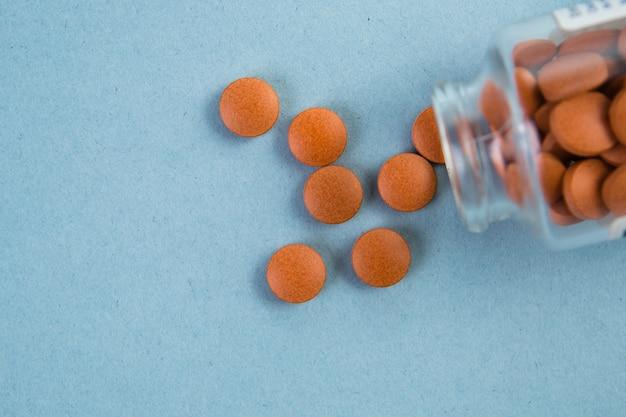 Frasco de vidrio con pastillas de color naranja derramándose sobre una superficie azul