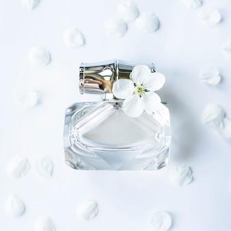 Un frasco de vidrio de perfume entre pétalos blancos de primavera.