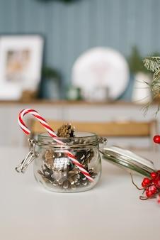 Frasco de vidrio con una tapa llena de conos de coníferas y un bastón de piruleta en la mesa de la cocina decorada para navidad