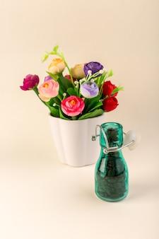Un frasco de vista frontal con café y flores sobre la mesa rosa, color café, semillas de flores
