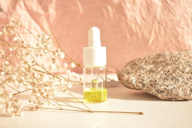 Frascos de aceite cosmético esencial en una botella de vidrio sobre una mesa blanca. aceite de aromaterapia, el concepto de cosmética natural.