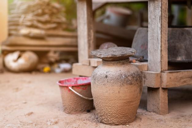 Frascos de barro viejos tailandeses recogen carbón usado con mesa de madera