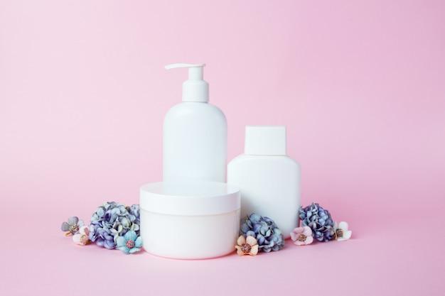 Frascos blancos de cosmeticos con flores en rosa.