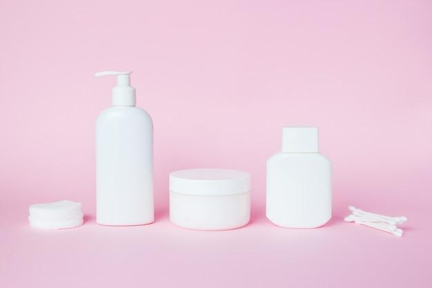 Frascos blancos de cosmeticos en rosa.