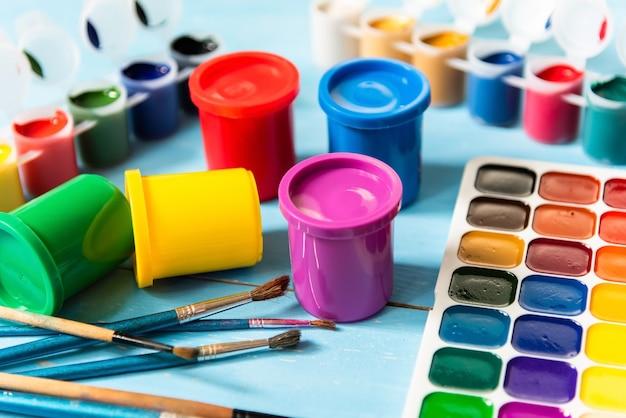 Frascos de colores con gouache y acuarelas sobre una superficie azul