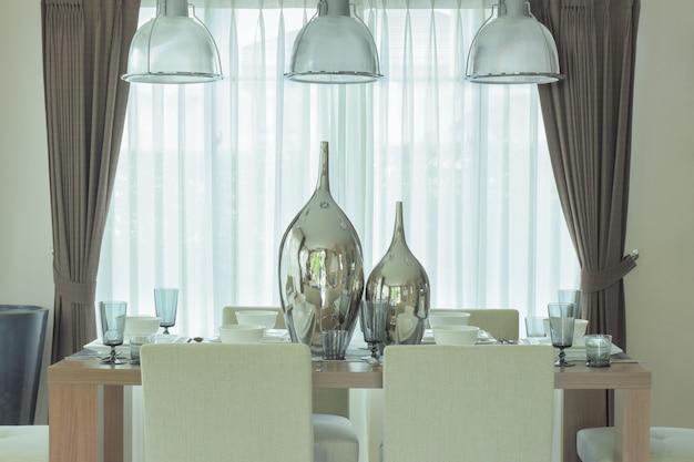 Frascos decorativos de plata en el centro de la mesa de comedor en una decoración moderna de estilo clásico
