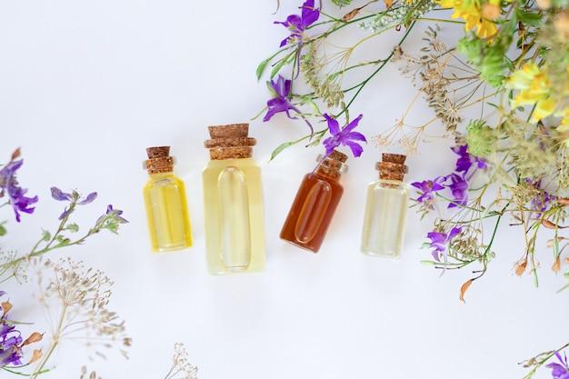 Frascos de diferentes aceites esenciales y flores silvestres curativas vista superior sobre fondo blanco.