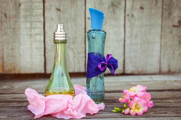 Frascos de perfume azul y verde cerca de flores fresia.
