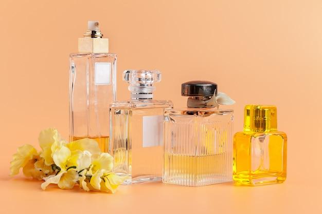 Frascos de perfume con pétalos de flores sobre beige