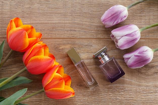 Frascos de perfume con tulipanes rojos y lilas en las tablas de madera