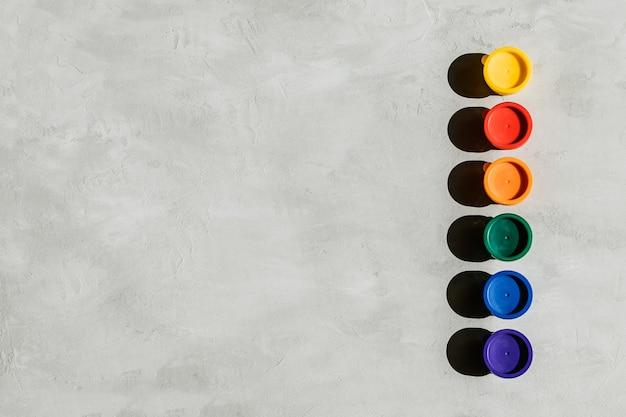Frascos de pinturas multicolores y sobre un hormigón gris