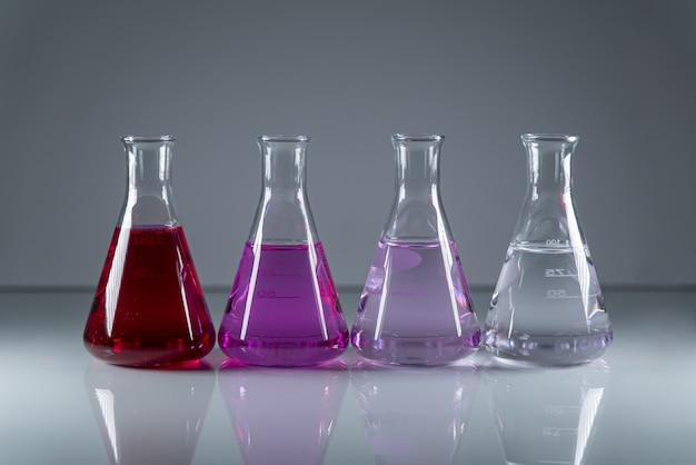 Frascos de química en una fila con líquido tóxico peligroso de diferentes colores.