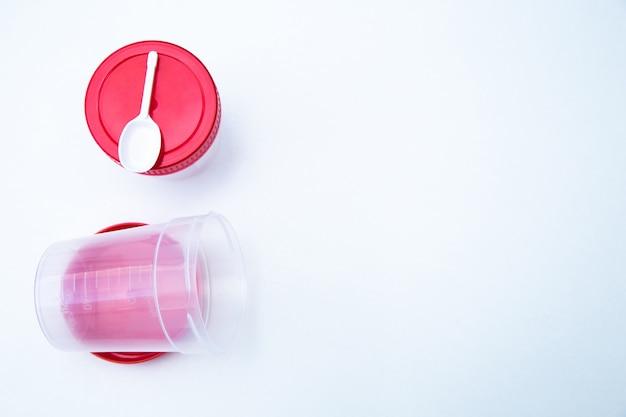 Frascos para recolectar pruebas con tapa roja y cuchara sobre fondo blanco foto de alta calidad