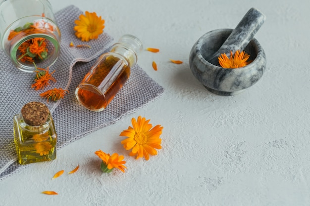 Frascos de tintura o infusión de caléndula y aceite esencial con flores de caléndula frescas y secas a la luz