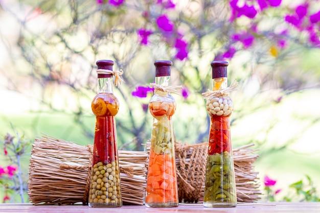 Frascos con verduras encurtidas en mesa de madera