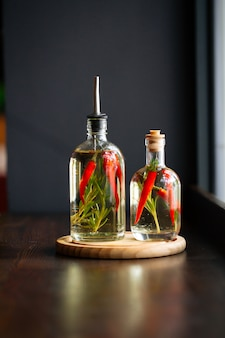 Frascos de vidrio con salsa de vinagre, pimienta y romero