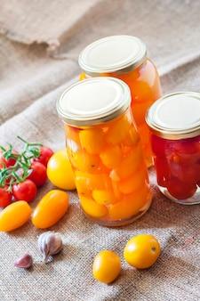 Frascos de vidrio con tomates en escabeche caseros, sellados con tapa de metal