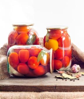 Frascos de vidrio con tomates rojos en escabeche, sellados con tapa de metal