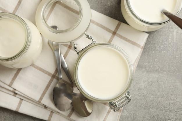 Frascos de vidrio de yogur, cucharas y servilletas en gris