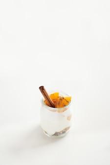 Frascos de yogurt griego con granola, canela y albaricoques enlatados