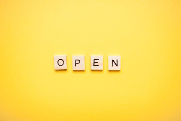 Frase abierta hecha de bloques de madera sobre un fondo amarillo claro. foto de alta calidad