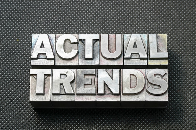 Frase de tendencias reales hecha de bloques de tipografía metálicos sobre superficie perforada negra