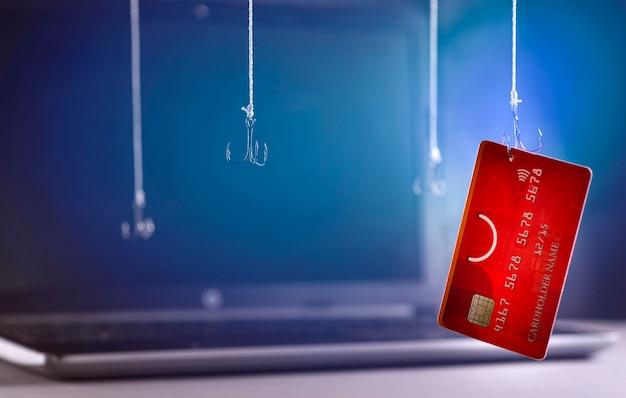 Fraude en internet utilizando tecnología informática, robo de dinero en internet, robo de datos de tarjetas de crédito. gancho de tarjeta de crédito enganchada sobre fondo de neón