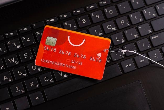 Fraude en internet utilizando tecnología informática, robo de dinero en internet, robo de datos de tarjetas de crédito. gancho de tarjeta de crédito enganchado sobre fondo de teclado de computadora