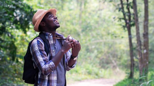 Freedom african man traveler con mochila de pie y sosteniendo la cámara de cine
