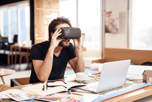 Freelance barbudo hombre usando realidad virtual en la computadora portátil.
