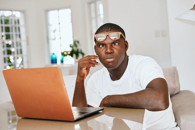 Freelance masculino afroamericano con laptop en casa
