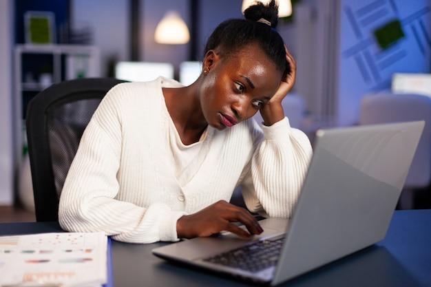 Freelancer africano agotado descansando la cabeza en la mano frente a la computadora portátil trabajando horas extras en la oficina de la empresa de puesta en marcha