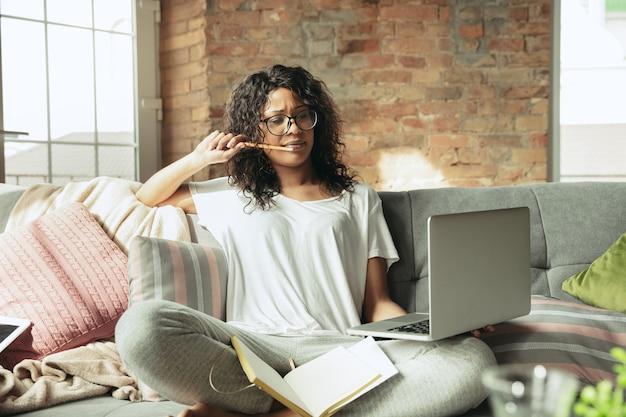 Freelancer afroamericana durante el trabajo en la oficina en casa mientras está en cuarentena