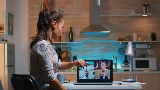 Freelancer apagando la computadora portátil durante el seminario web en medio de una videoconferencia sentado en la cocina trabajando hasta altas horas de la noche de forma remota. uso de la red inalámbrica de tecnología moderna