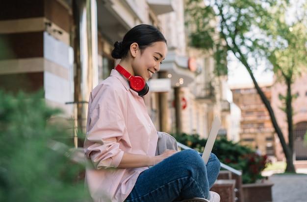 Freelancer asiático usando laptop, escribiendo en el teclado, blogueando. estudiante coreano estudiando al aire libre