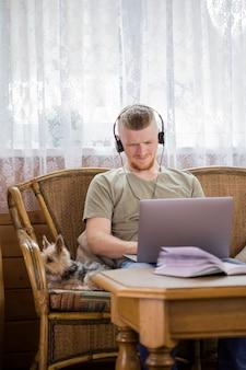 Freelancer barbudo que trabaja de forma remota desde casa usando una computadora portátil y pensando en la solución del problema
