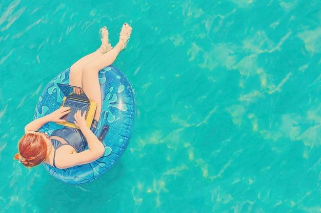 El freelancer bonito joven de la mujer está flotando en el mar o en la piscina en un círculo de la natación