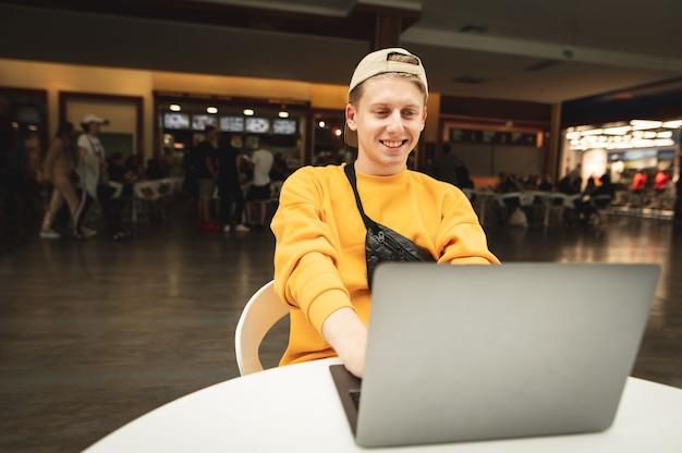 Freelancer feliz se sienta a la mesa en un patio de comidas en un centro comercial