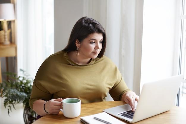 Freelancer gordita atractiva joven vestida con elegante suéter y pendientes redondos trabajando frente a la computadora portátil abierta, sentado en el acogedor interior de la oficina en casa, tomando café, navegando por sitios web