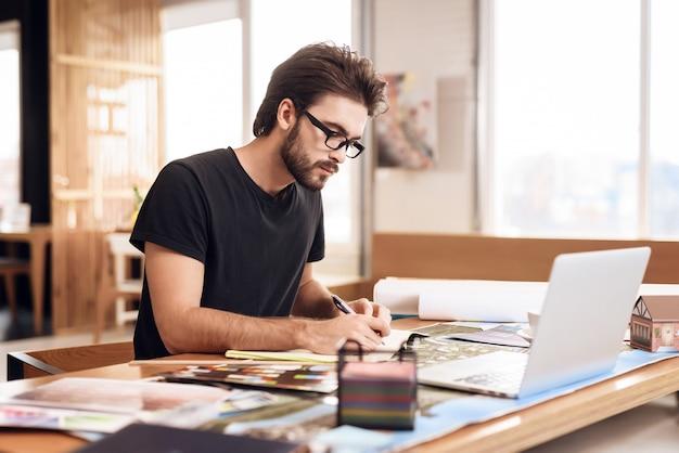 Freelancer hombre barbudo tomando notas en la computadora portátil.