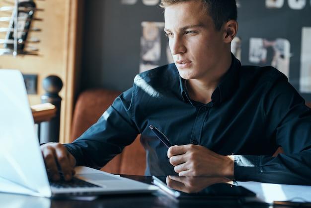 Freelancer de hombre de negocios con laptop en café en el modelo de taza de café de documentos de administrador de mesa.