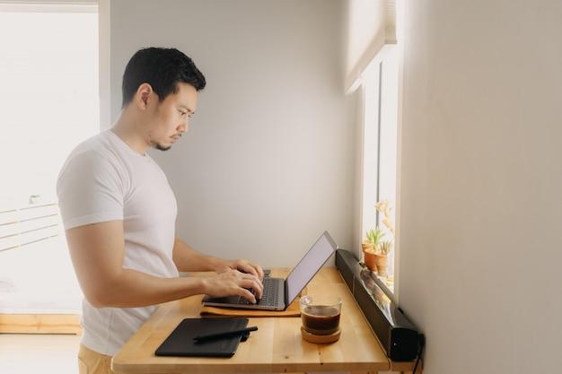 Freelancer hombre está trabajando en su computadora portátil en su apartamento. concepto de trabajos creativos freelance.