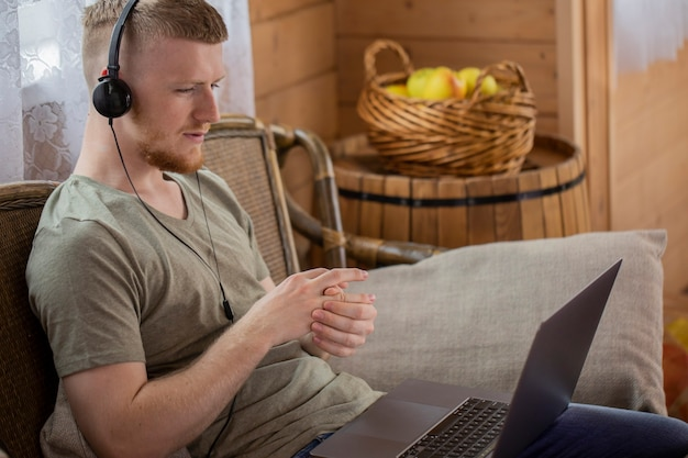 Freelancer masculino guapo comunicándose en la red social y trabajando de forma remota desde casa