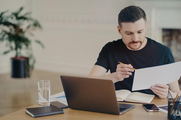Freelancer masculino ocupado guapo o hombre de negocios en camiseta negra analizando documento con información o informe de ventas mientras trabaja de forma remota desde casa, sentado en el escritorio con computadora portátil y otros suuplies de oficina