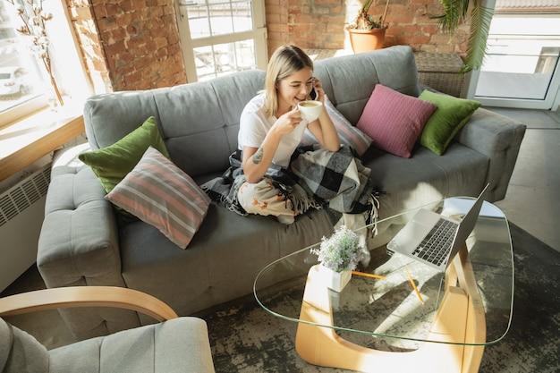 Freelancer mujer caucásica durante el trabajo en la oficina en casa mientras está en cuarentena