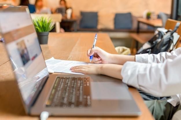 Freelancer rellenando el formulario de documento con el portátil abierto en la mesa de madera.